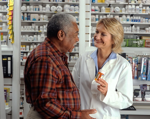Here we see a man in a pharmacy discussing his pain treatment with a lady pharmacist.